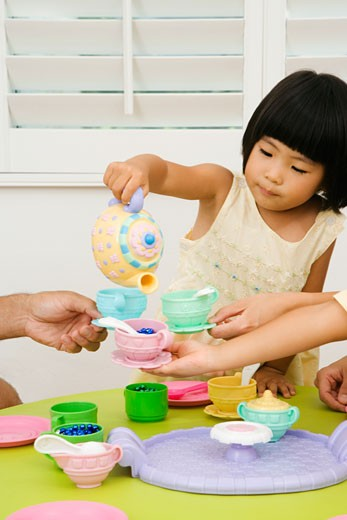 Asian girl and family playing with toy tea set : Stock Photo