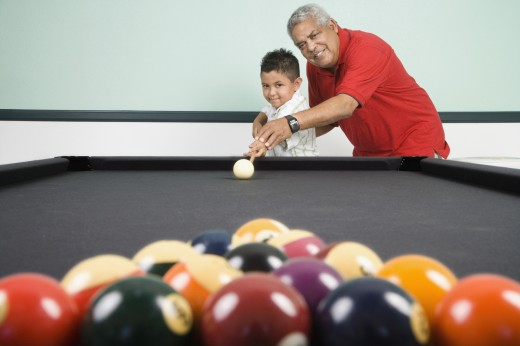 Hispanic grandfather helping grandson play pool : Stock Photo