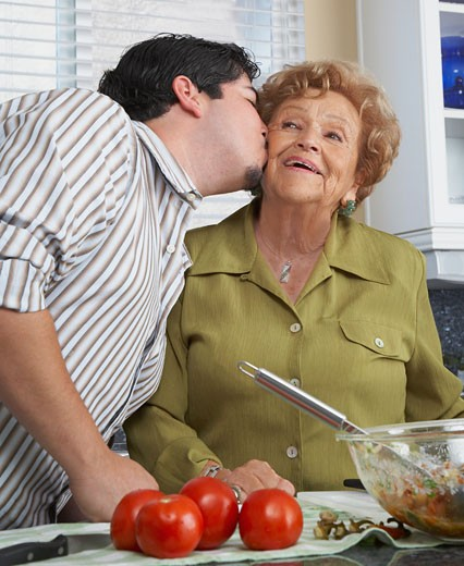 Hispanic man kissing mother on cheek : Stock Photo