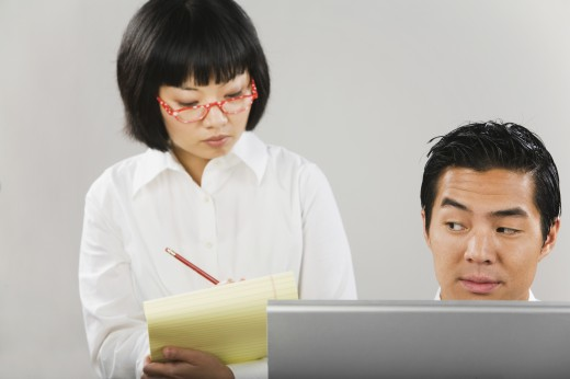 Stock Photo: 1589R-33206 Asian woman taking notes next to man at computer