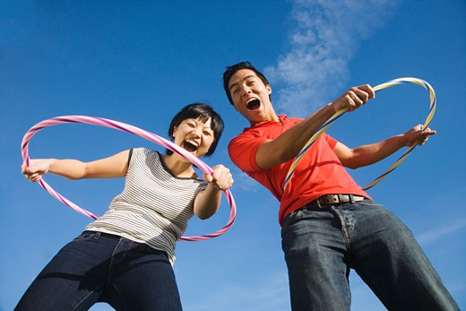 Asian couple playing with hula hoops : Stock Photo