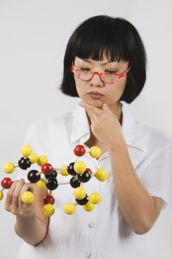 Stock Photo: 1589R-33259 Asian female scientist looking at chemical model