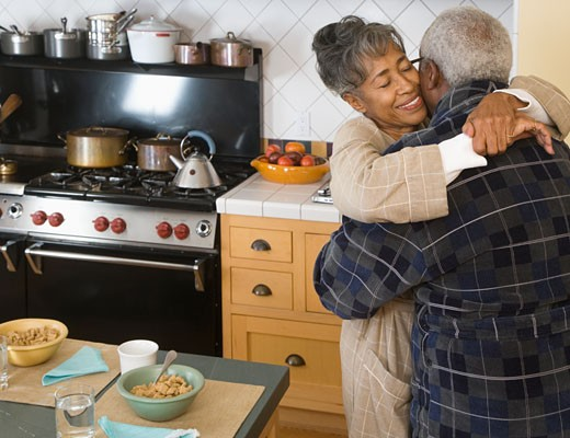 Stock Photo: 1589R-33378 Senior African couple hugging in kitchen