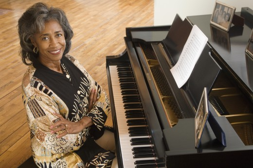 Senior African woman sitting at piano : Stock Photo