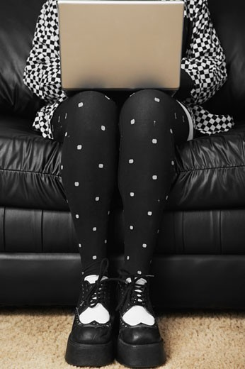 Stock Photo: 1589R-33420 Woman in funky tights typing on laptop