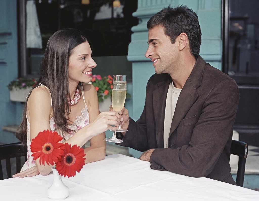Stock Photo: 1589R-33542 Hispanic couple toasting with champagne at outdoor cafe