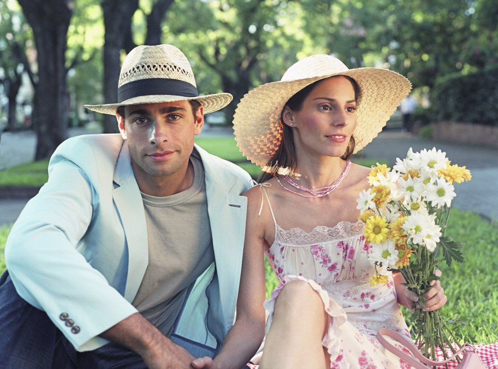 Stock Photo: 1589R-33554 Hispanic couple holding wildflowers at park