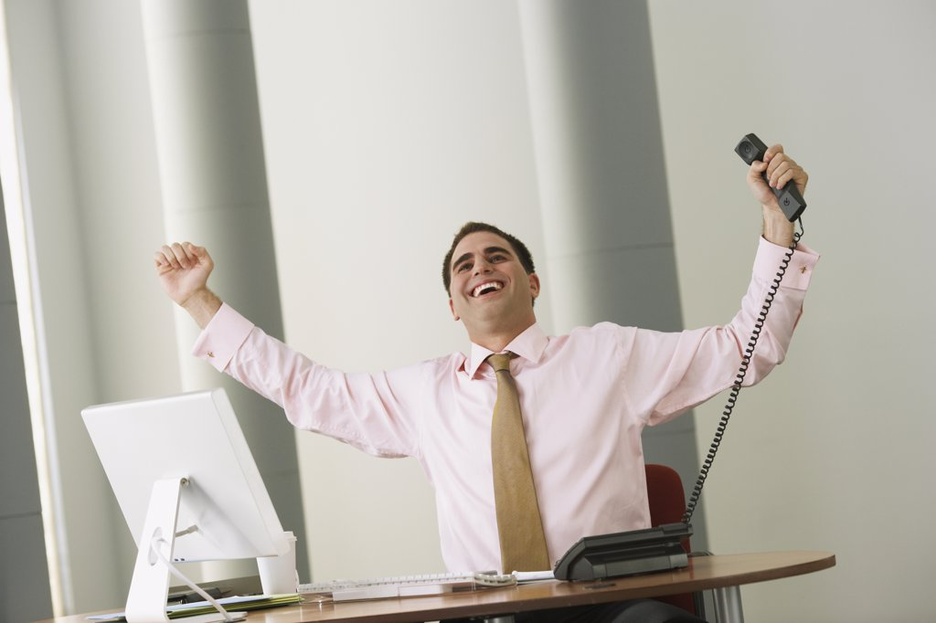 Middle Eastern businessman cheering at desk : Stock Photo