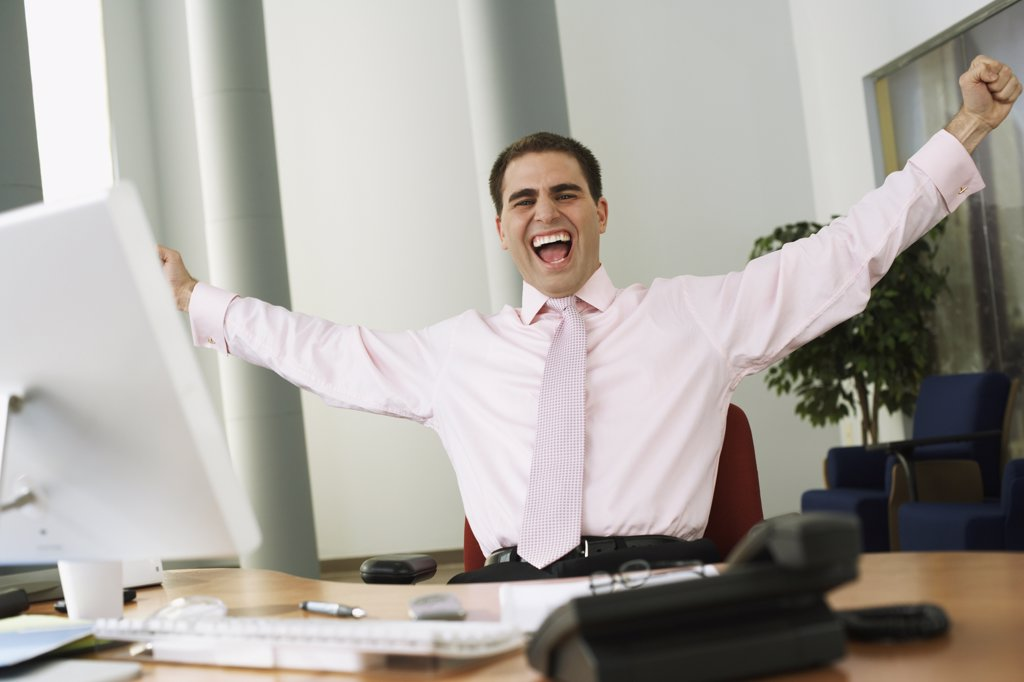 Stock Photo: 1589R-33807 Middle Eastern businessman cheering at desk