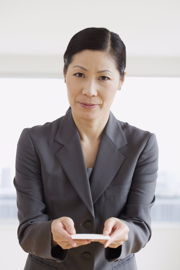 Stock Photo: 1589R-33957 Middle-aged Asian businesswoman offering business card