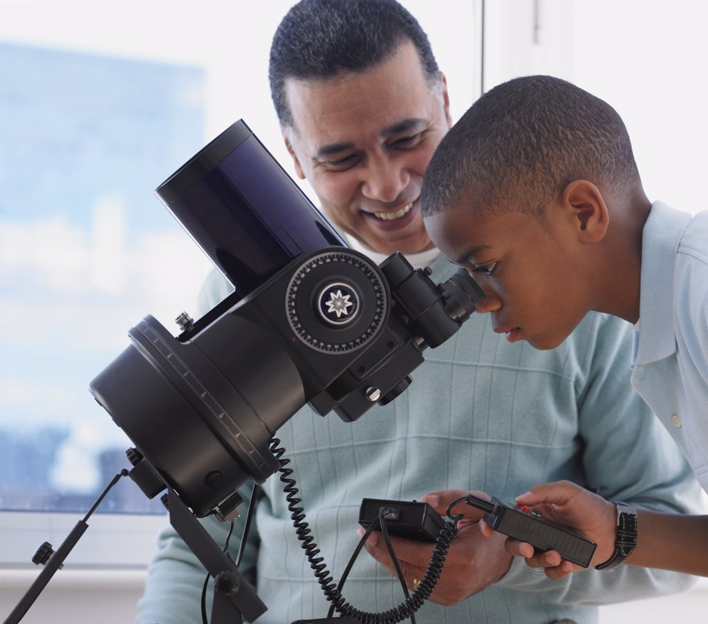 African boy looking into microscope with father : Stock Photo