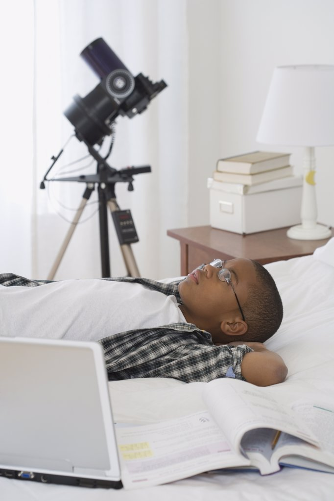 Stock Photo: 1589R-33991 African boy laying on bed next to laptop and school books