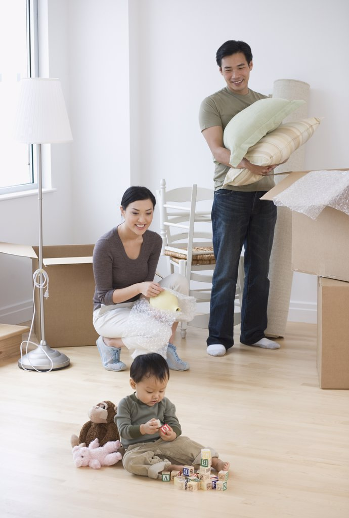 Stock Photo: 1589R-34088 Asian parents watching baby play with blocks on floor
