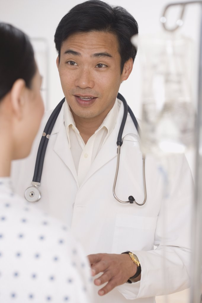 Stock Photo: 1589R-34112 Asian male doctor talking to patient