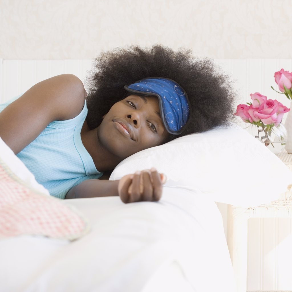 Stock Photo: 1589R-34225 African woman wearing eye mask in bed