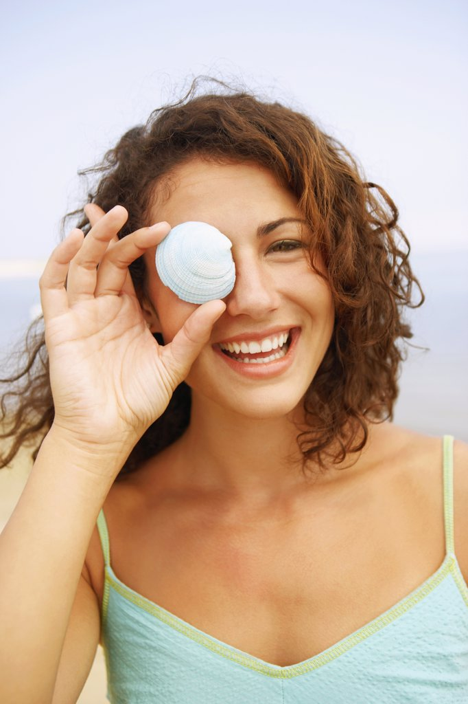 Stock Photo: 1589R-34309 Woman holding seashell over eye