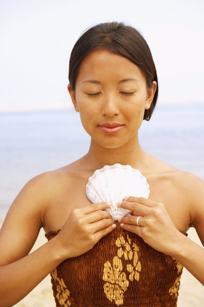 Asian woman holding seashell against chest : Stock Photo