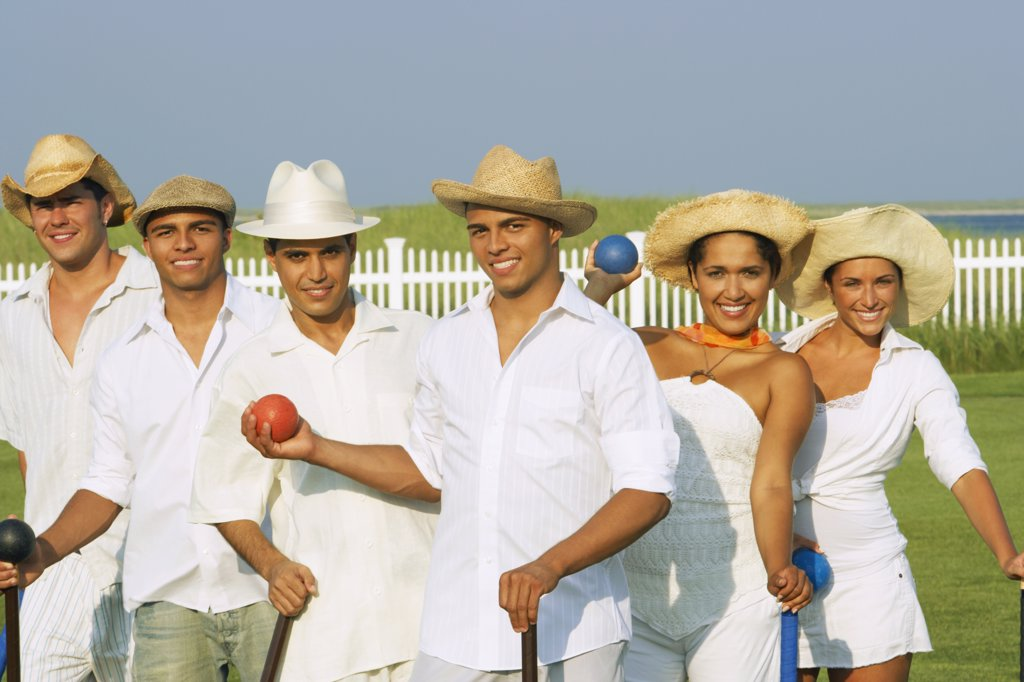 Multi-ethnic friends playing croquet : Stock Photo
