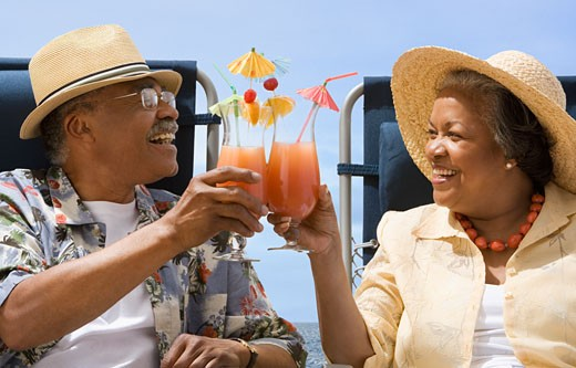 Stock Photo: 1589R-35041 Senior African couple toasting with tropical cocktails