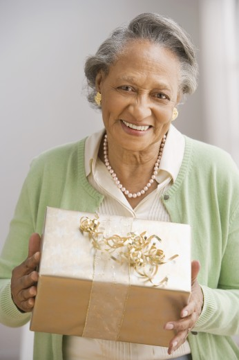 Senior African woman holding gift : Stock Photo
