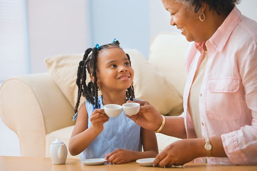 Stock Photo: 1589R-35121 African grandmother and granddaughter playing with tea set