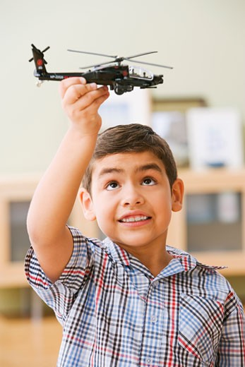 Stock Photo: 1589R-35159 Hispanic boy playing with toy helicopter