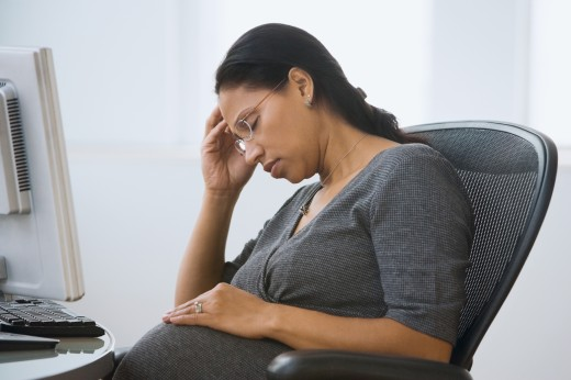 Pregnant Hispanic businesswoman resting at desk : Stock Photo