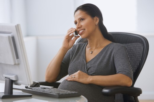 Stock Photo: 1589R-35181 Pregnant Hispanic businesswoman talking on cell phone