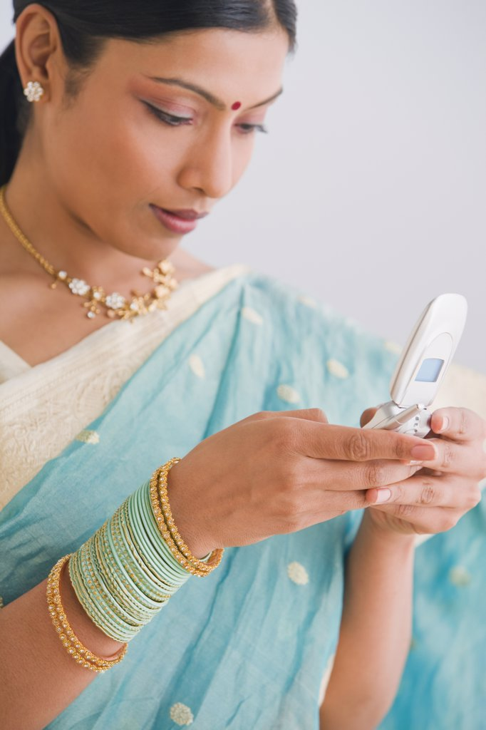 Indian woman in traditional clothing using cell phone : Stock Photo