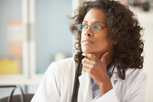 Stock Photo: 1589R-35393 African female doctor looking to side with chin in hand