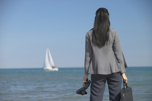 Stock Photo: 1589R-35424 Businesswoman looking out over water with sailboat