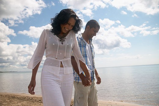 Indian couple holding hands and smiling at beach : Stock Photo