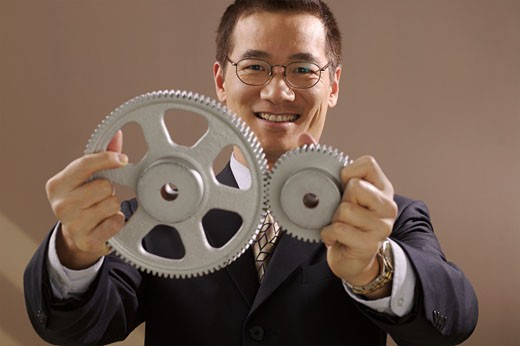 Asian businessman holding gear wheels : Stock Photo