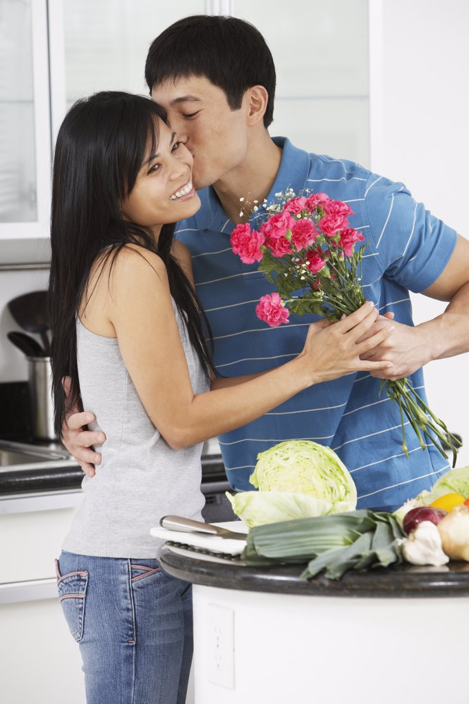 Asian man kissing girlfriend and giving her flowers in kitchen : Stock Photo