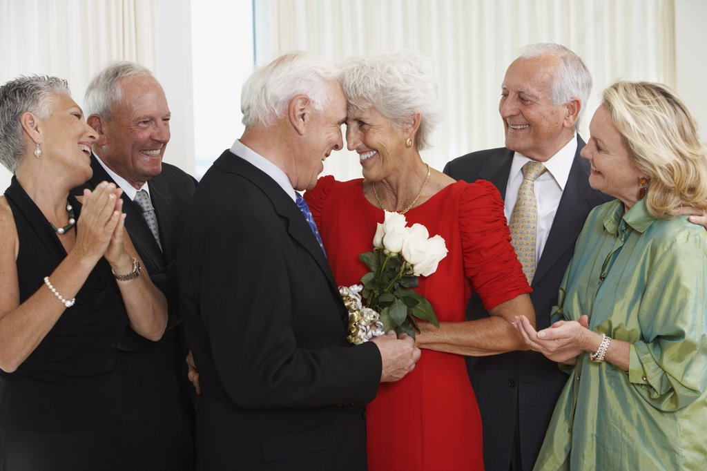Stock Photo: 1589R-35965 Senior man giving wife bouquet of flowers while friends watch