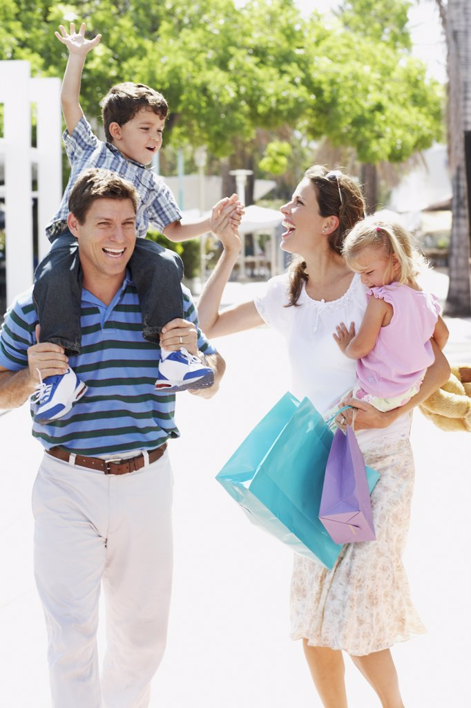 Stock Photo: 1589R-35970 Hispanic family walking with shopping bags outdoors