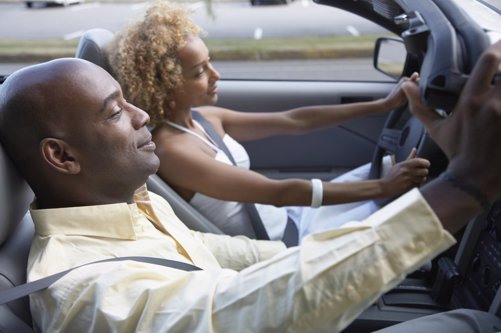 African couple driving convertible car : Stock Photo