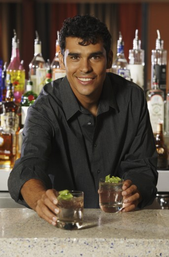 Hispanic male bartender serving drinks : Stock Photo