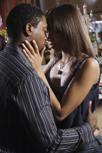 African couple hugging at bar : Stock Photo