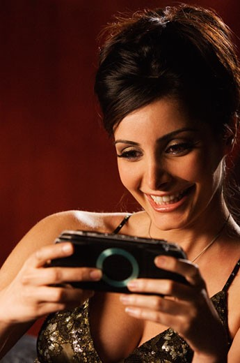 Middle Eastern woman playing hand held video game : Stock Photo