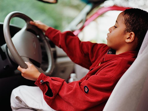 Stock Photo: 1589R-36443 African boy pretending to drive car