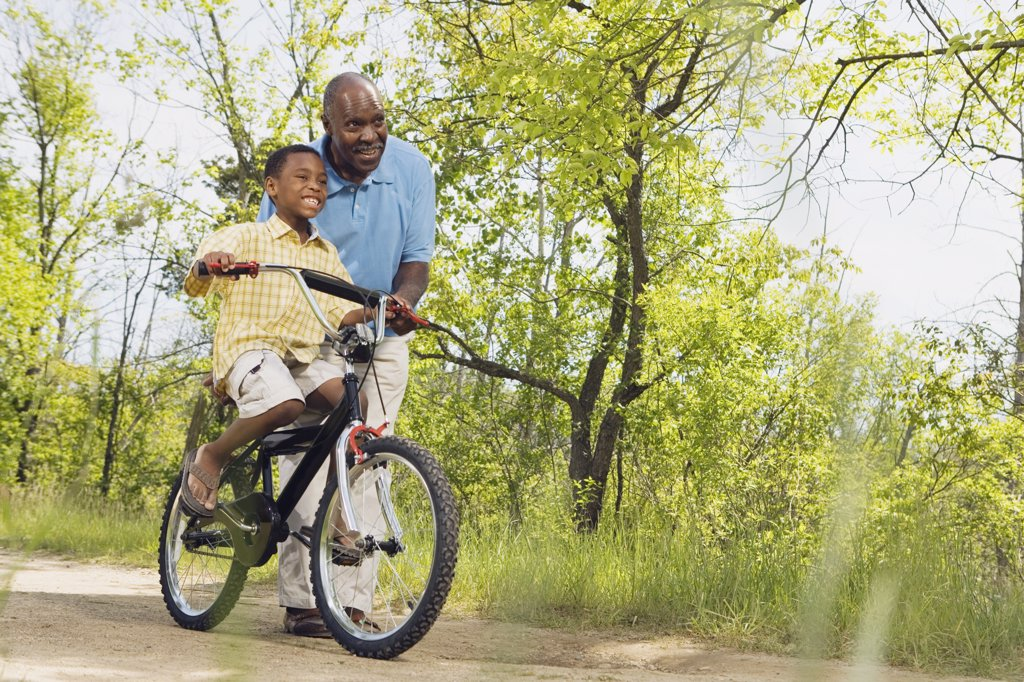 African grandfather teaching grandson to ride a bicycle in park : Stock Photo