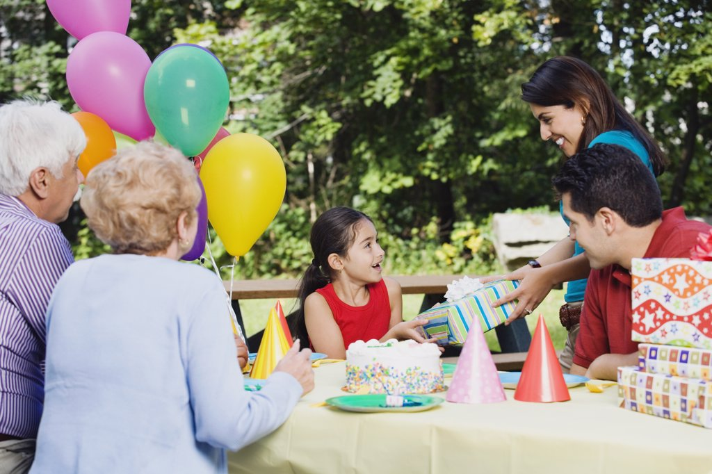 Stock Photo: 1589R-36532 Hispanic girl receiving gifts at birthday party