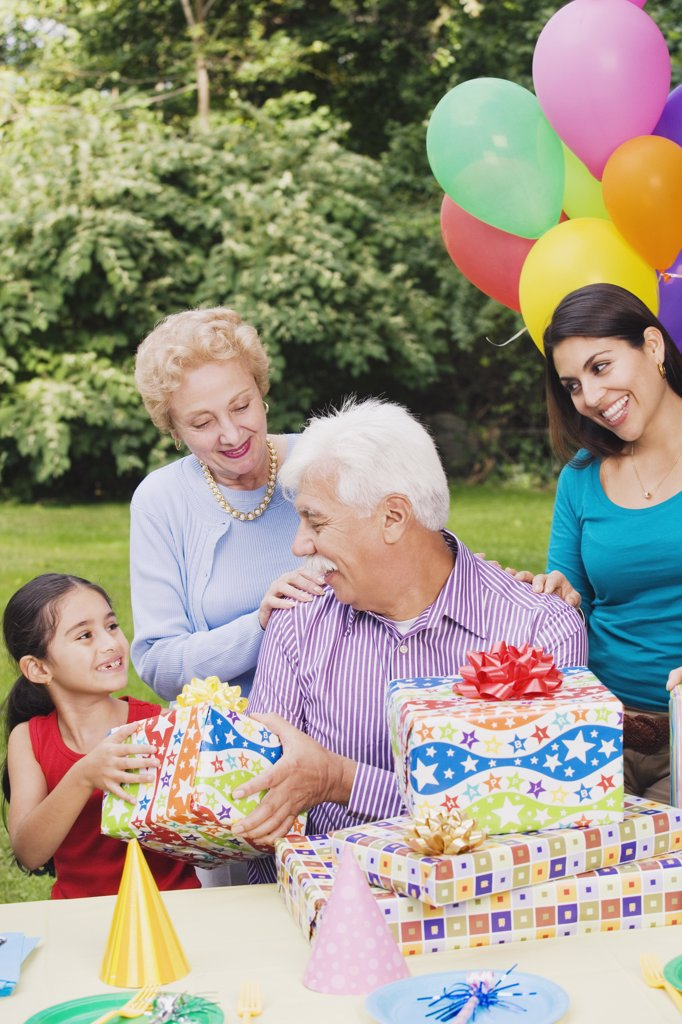Stock Photo: 1589R-36539 Senior Hispanic man receiving gifts at birthday party