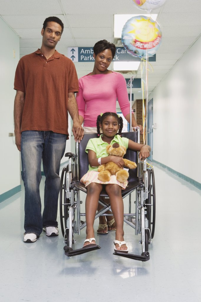 Stock Photo: 1589R-36601 African girl smiling in wheelchair with parents in hospital