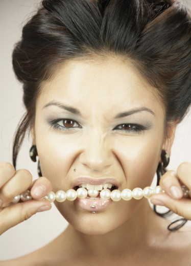 Stock Photo: 1589R-36616 Woman with hair up biting pearl necklace