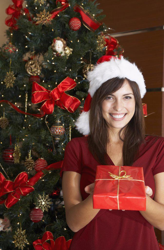 Hispanic woman holding Christmas gift : Stock Photo