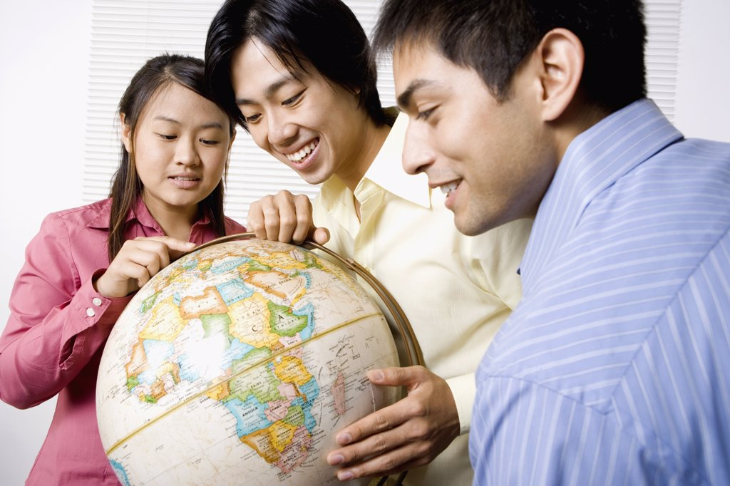 Three friends looking at globe : Stock Photo