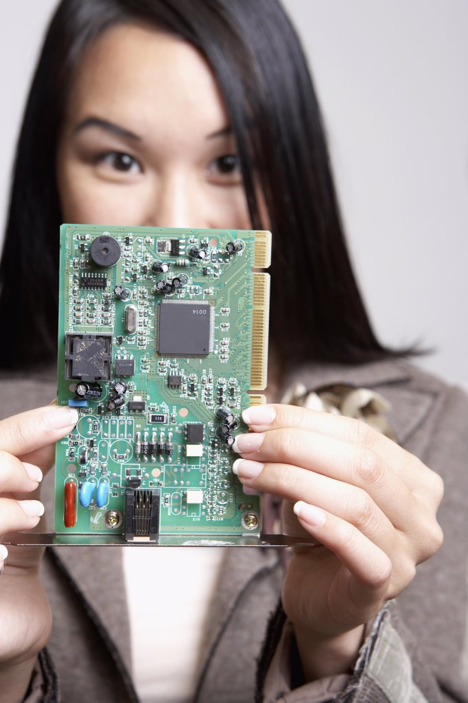 Asian businesswoman holding up computer circuit board : Stock Photo