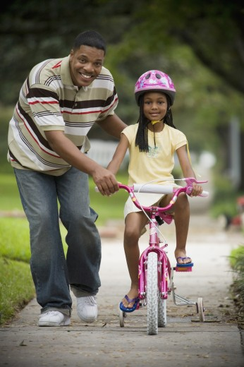 African father helping daughter ride bicycle : Stock Photo